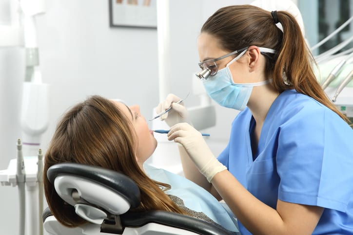 Dentist wearing eyeglasses gloves and mask examining a patient teeth with a dental probe and a mirror in a clinic box with equipment in the background