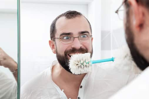 man brushing teeth with toilet scrubber